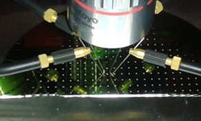 Se observan las puntas de prueba de la estación de prueba sobre los contactos eléctricos del microcalefactor y de la película sensible.